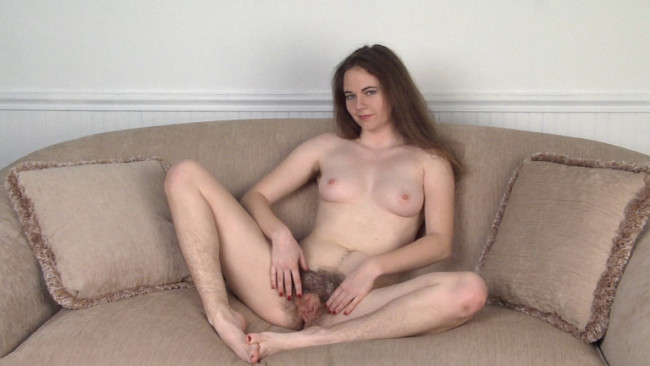Hairy amateur brunette Camille does a striptease on the couch and spreads her pussy