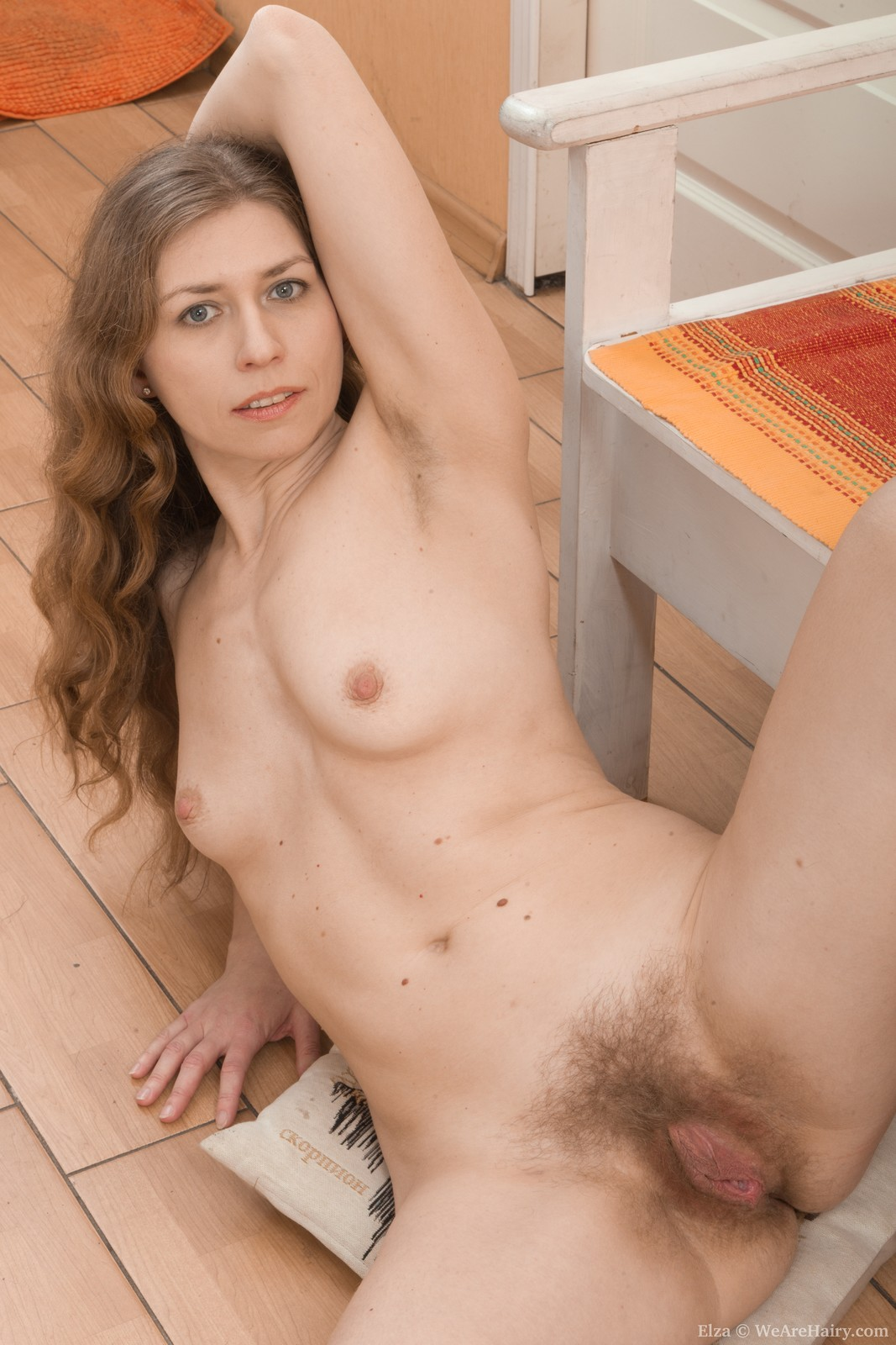 Elza strips naked in bedroom and models on a chair 7